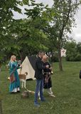 Reconstruction of medieval games: soldiers in armor and cold steel. The ladies are shooting from the bow. Stock Image