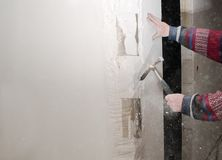 Reconstruction and renovation, craftsman removes a part of the wall with a hammer for the interior fitting in a construction site royalty free stock photos