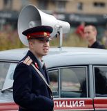 A reconstructor in the Soviet uniform of a police officer at the Moskvich-401 car at an exhibition of old transport. Stock Photo