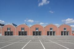 Reconverted factory behind an empty parking  Stock Photo