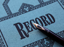 Record. Closeup of a fancy cloth record book cover with a fountain pen Royalty Free Stock Image