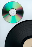 Record and cd. Close up of a cd and partial record over white background Royalty Free Stock Image