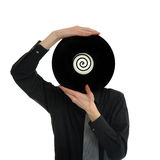 Record Head. Man in suit and tie holds up a record LP to his head Stock Image