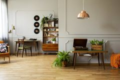 Record player and plant on wooden table in grey apartment interior with lamp and vinyl. Real photo stock photos