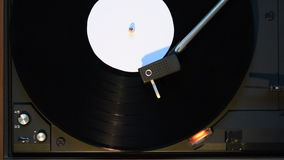 Record player playing an old fashioned vintage vinyl record. The record is ending and the needle is taken off the vinyl stock footage