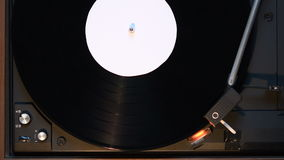 Record player playing an old fashioned vintage vinyl record. The needle is being put on the record stock footage