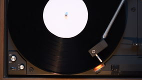 Record player playing an old fashioned vintage vinyl record. The needle is being put on the record stock video footage