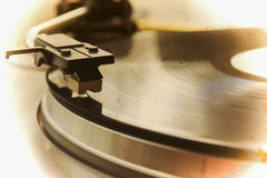 Record player stylus in sepia tone. Record player stylus on a rotating disc Stock Photos