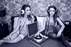 Record playing disco twins on bed. Fantastic conceptual image of a beautiful sexy disco woman on a bed playing records filmed twice interacting with herself Stock Images