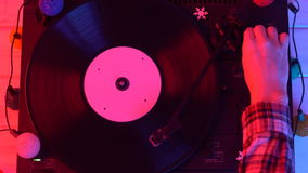 A record starts spinning - then a womans hand drops the needle and turns off stock video footage