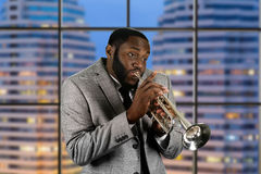 Record studio in megalopolis. Professional musician on stage. Late evening trumpet performance. Black man playing trumpet music. Record studio in megalopolis royalty free stock photos