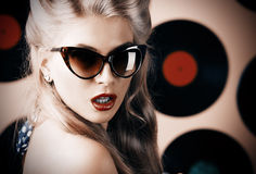 Record studio. Portrait of a charming pin-up woman with retro hairstyle and make-up posing with vinyl record Stock Photography