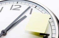 Recordatorio de la cita Reloj con la nota pegajosa amarilla Fotografía de archivo libre de regalías