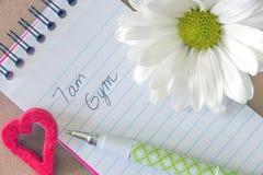 Recordatorio del entrenamiento del gimnasio en el nuevo cuaderno, con deco de la flor y del corazón Fotos de archivo