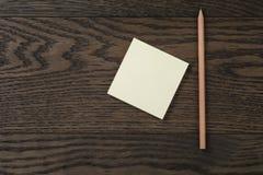 Recordatorio pegajoso de la nota en la tabla de madera de roble con el lápiz Foto de archivo