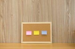 recordatorio pegajoso de las notas en tablero del corcho corkboard del boletín fotos de archivo