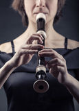 Recorder. Close-up of a woman playing on a recorder on a black background Royalty Free Stock Images