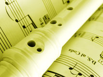 Recorder and music score. A still life image of a recorder laid across a page of music score.  Vertical image, processed to golden yellow monochrome for mood Royalty Free Stock Photography