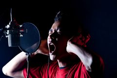 Recording. The singer is focus on his recordings Stock Photos