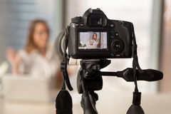 Recording business video on modern DSLR camera. Close up image of camera on tripod with smiling woman on back screen and blurred scene on background. Recording stock images