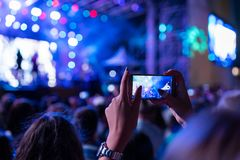 Recording a concert on a mobile phone from the crowd. Concert photography from the crowd royalty free stock photo