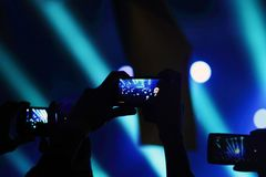 Recording of the concert on the phone. Silhouette of hands holding a mobile phone and taking a video of a rock concert. Low light photos, some grain present royalty free stock images