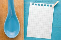For recording cooking recipes and kitchens. A piece of paper with a pin on turquoise yellow-blue wooden Board and clay spoon stock images