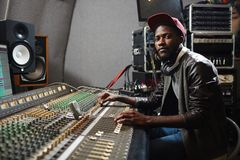 Recording rap. Modern young singer in rapper attire working in audio studio by recording equipment Stock Photography