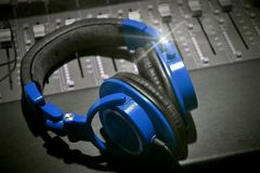 Recording studio headphones black white and blue. Music recording studio table close up black and white music photography headphones professional equipment stock photography
