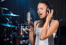 Recording Studio. Portrait of young woman recording a song in a professional studio Royalty Free Stock Photography