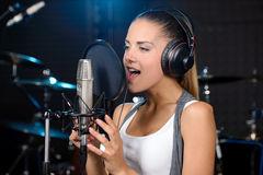 Recording Studio. Portrait of young woman recording a song in a professional studio Royalty Free Stock Image