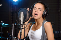 Recording Studio. Portrait of young woman recording a song in a professional studio Royalty Free Stock Photo