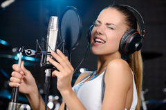 Recording Studio. Portrait of young woman recording a song in a professional studio stock photo