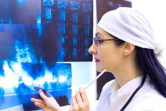 Recordings of X-ray and magnetic resonance imaging. Young female doctor standing at the table with X-ray,photography Royalty Free Stock Photography