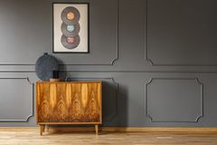 Records on grey wall with molding above wooden cabinet in vintage living room interior. Real photo. Place your lamp here stock photo