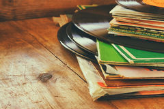 Records stack with record on top over wooden table. vintage filtered.  royalty free stock photo