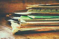 Records stack with record on top over wooden table. vintage filtered Stock Image
