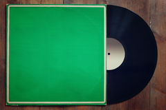 Records stack with record on top over wooden table. vintage filtered Stock Photos