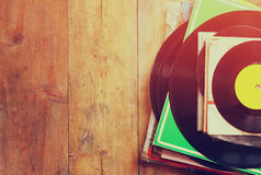 Records stack with record on top over wooden table. vintage filtered Royalty Free Stock Photos