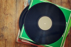 Records stack with record on top over wooden table. vintage filtered Stock Photography