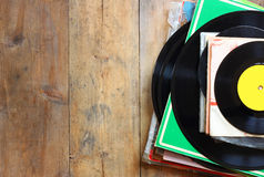 Records stack with record on top over wooden table. vintage filtered Royalty Free Stock Photography