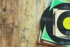 Records stack with record on top over wooden table. vintage filtered.  royalty free stock images