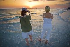Recorriendo la playa en la puesta del sol Foto de archivo libre de regalías