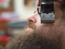 Recorte de la barba con las podadoras en una peluquería de caballeros fotos de archivo libres de regalías