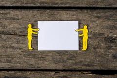 Recortes de papel de dos hombres que llevan a cabo una muestra en blanco imagen de archivo libre de regalías