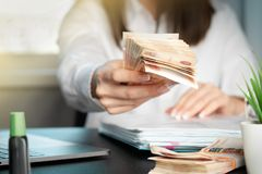 Woman working at office. Recount of bank note. Hand giving money close up. Payment of goods stock images