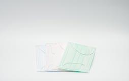 Recouvrement jetable de masque protecteur de boucle verte, rose, bleu-clair et blanche d'oreille, utilisé pour couvrir la bouche  Photos libres de droits