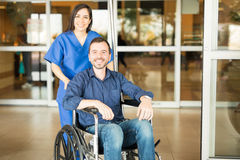 Recovered patient leaving the hospital. Portrait of a young Hispanic patient leaving the hospital in a wheelchair after a full recovery Royalty Free Stock Images