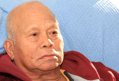 Recovering. Face shot of a senior Filipino man sat up on a recovery bed with a flash of sunshine on his side Royalty Free Stock Photos