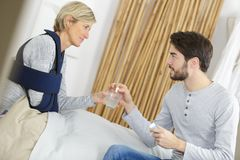 Recovering lady with home help giving pills stock images